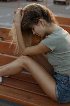 Mooie jonge sexy hipster vrouw met krullend haar in denim shorts en t-short zittend op een bankje