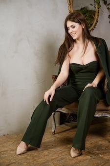 Mooie jonge sexy vrouw in groen pak zit in een stoel