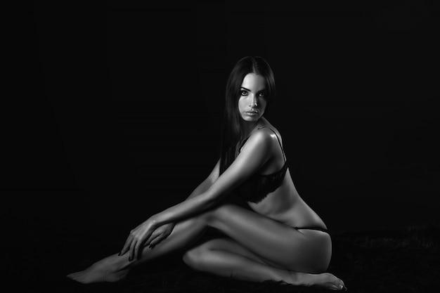 Mooie jonge sexy vrouw in zwart ondergoed, zwart-witte foto