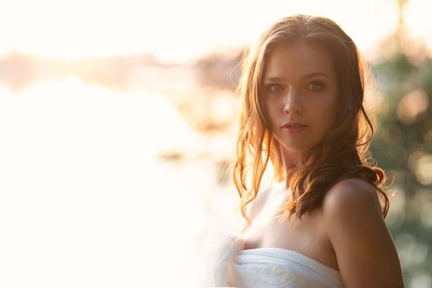 Mooie jonge sexy vrouw loopt langs de rivier bij zonsondergang