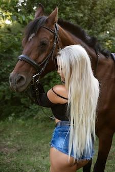 Mooie jonge sexy vrouw met lang wit haar in korte broek staat met een paard