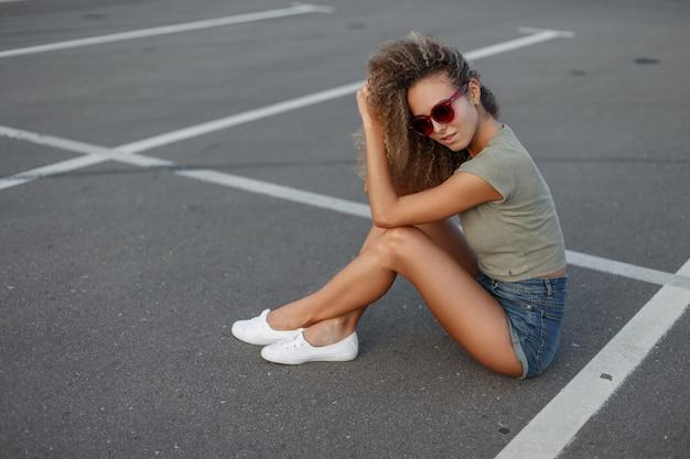 Mooie jonge slanke hipster krullend meisje met zonnebril in jeans kleding met modieuze witte sneakers zittend op asfalt op straat