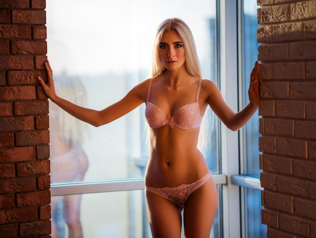 Mooie jonge slanke langharige blonde vrouw in elegant ondergoed poseren tegen de achtergrond van een groot raam tussen twee bakstenen muren
