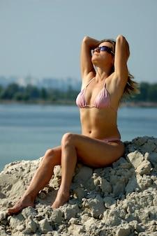 Mooie jonge slanke sexy vrouw in een roze zwembroek en zonnebril zit op het zand, geniet van de warme zomerzon op een zonnige zomerdag tijdens vakantie