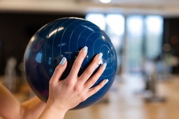 Mooie jonge slanke vrouw in sportwear doet wat gymnastiek in de sportschool met medball