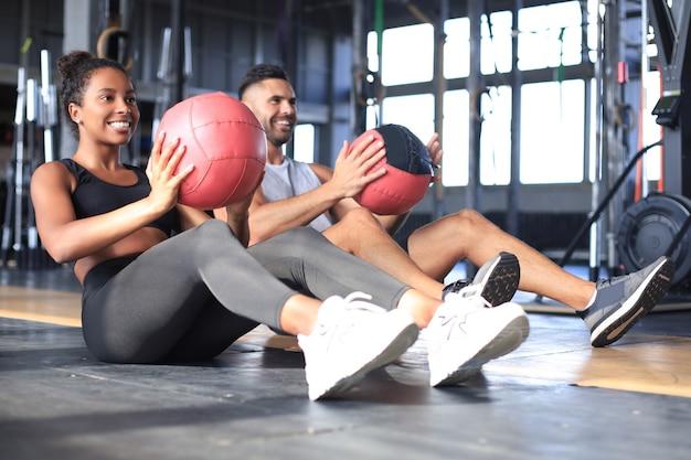 Mooie jonge sport paar werkt met medicijnbal in de sportschool.