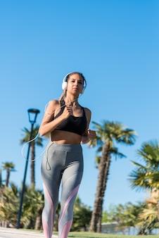 Mooie jonge sporten vrouw loopt joggen in een park buitenshuis luisteren muziek