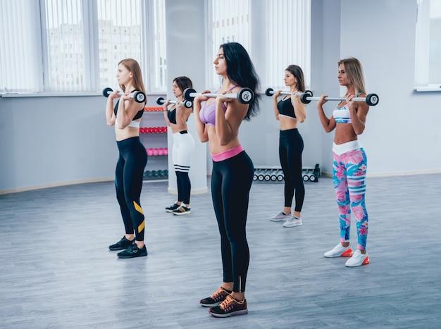 Mooie jonge sportenvrouwen die spieren met domoren in gymnastiek oppompen.