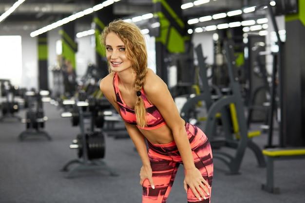 Mooie jonge sportieve vrouw die sportoefeningen in gymnastiek doet. fitness.
