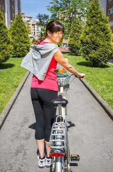 Mooie jonge sportieve vrouw met boodschappen in een mandfiets op een zonnige zomerdag