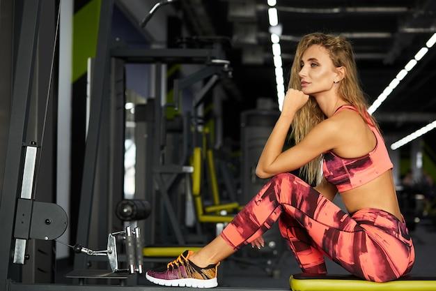 Mooie jonge sportieve vrouwenzitting op oefeningsmachine in gymnastiek. pauzeer na een zware training. fitness. gezonde levensstijl.