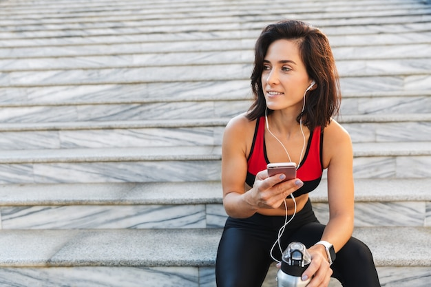 Mooie jonge sportvrouw die mobiele telefoon houdt, aan muziek met oortelefoons, drinkwater luistert