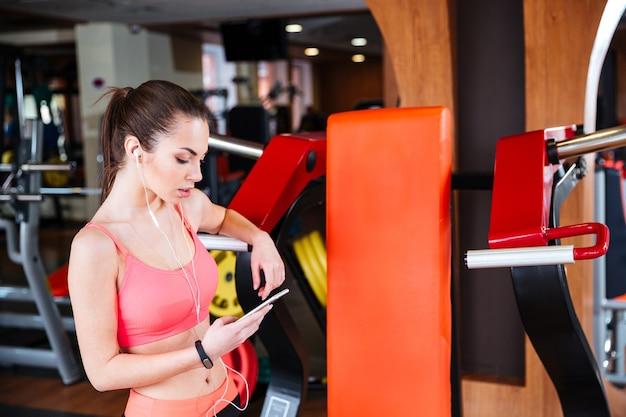Mooie jonge sportvrouw die naar muziek luistert en mobiele telefoon gebruikt in de sportschool