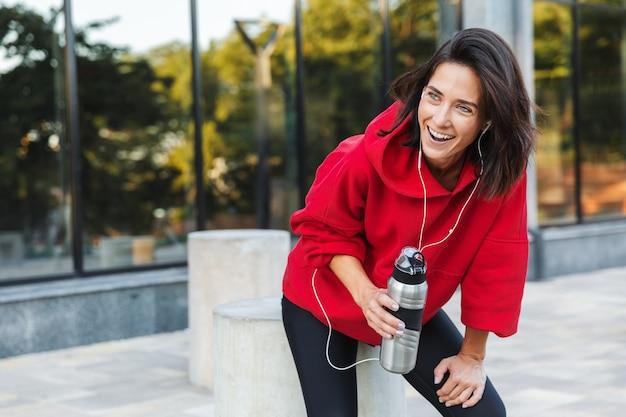 Mooie jonge sportvrouw luisteren naar muziek met koptelefoon, tijdens het rusten na het sporten, met waterfles