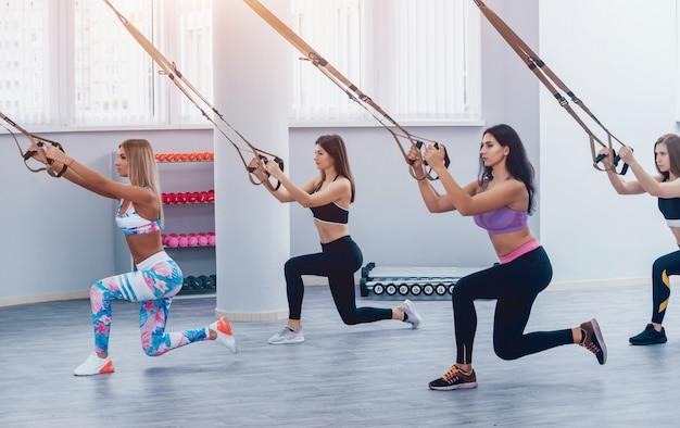 Mooie jonge sportvrouwen trainen met trx in de sportschool