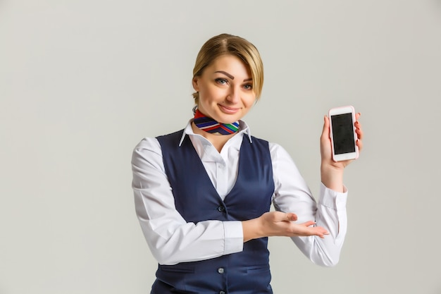 Mooie jonge stewardess die een slimme telefoon houdt die op wit wordt geïsoleerd