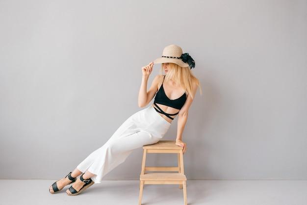 Mooie jonge stijlvolle blonde model poseren op trapladder in studio