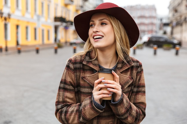 Mooie jonge stijlvolle blonde vrouw die een jas draagt die buiten loopt, met afhaalmaaltijden koffiekopje