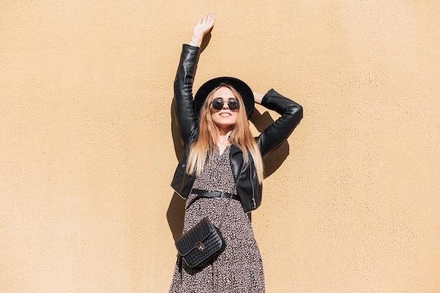 Mooie jonge stijlvolle gelukkig meisje met zonnebril en een zwarte hoed in een mode vintage jurk met een leren jas staat in de buurt van een gele muur op een zonnige dag