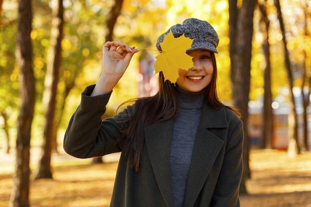Mooie jonge stijlvolle gelukkige vrouw met een glimlach in een modieuze jas met een vintage hoed met een geel herfstblad bedekt haar gezicht in het park