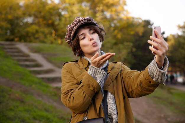 Mooie jonge stijlvolle kortharige brunette vrouw haar lippen vouwen en lucht kus blazen terwijl het maken van foto van zichzelf, staande over wazig park op warme herfstdag