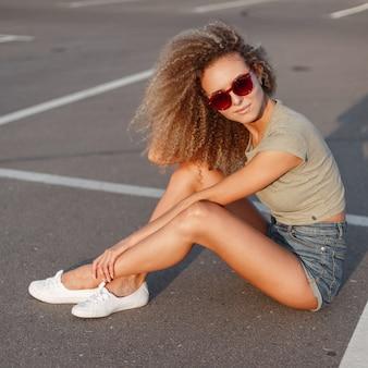 Mooie jonge stijlvolle trendy hipster vrouw met krullend kapsel met modieuze zonnebril in mode denim jeans broek in witte sneakers zittend op het asfalt op zonnige dag