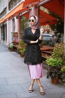 Mooie jonge stijlvolle vrouw in een sjaal staat op haar hoofd en zonnebril staat op straat in de buurt van een café
