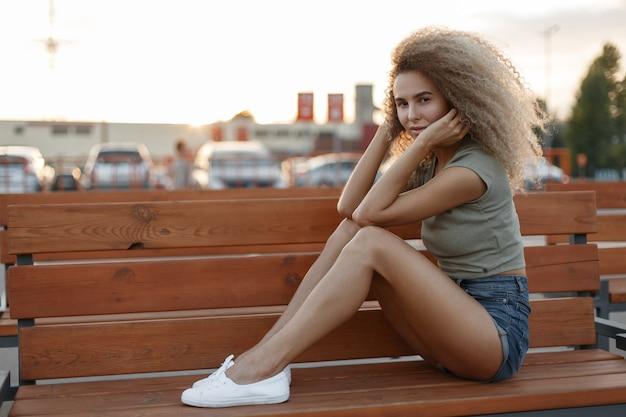 Mooie jonge stijlvolle vrouw in mode jeans korte broek met sexy benen en witte schoenen zit op een bankje op straat