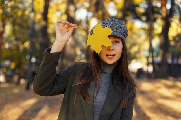 Mooie jonge stijlvolle vrouw in modieuze vintage kleding heeft betrekking op haar gezicht met een gele herfstblad in het park