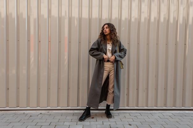 Mooie jonge stijlvolle vrouw model met krullend haar in een modieuze lange jas met laarzen rechtzetten haar riem in de buurt van een metalen wand. vrouwelijke casual mode en stijl