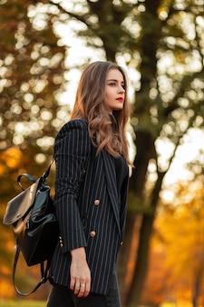 Mooie jonge stijlvolle zakelijke vrouwenmodel in een mode vintage pak met een blazer en een leren rugzak wandelingen in de natuur met een kleurrijk geel herfstblad bij zonsondergang