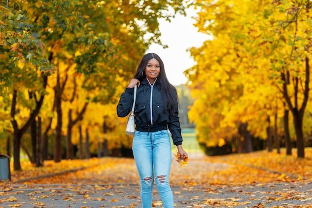 Mooie jonge stijlvolle zwarte canadese vrouw in modieuze kleding met een casual jas en spijkerbroek met een handtas loopt in een herfstpark met kleurrijke gouden herfstbladeren