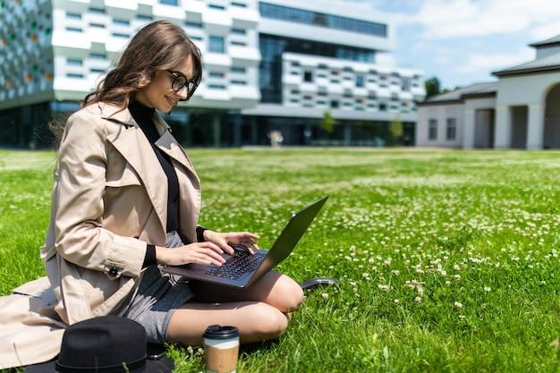 Mooie jonge student die laptop op gras in campus met behulp van