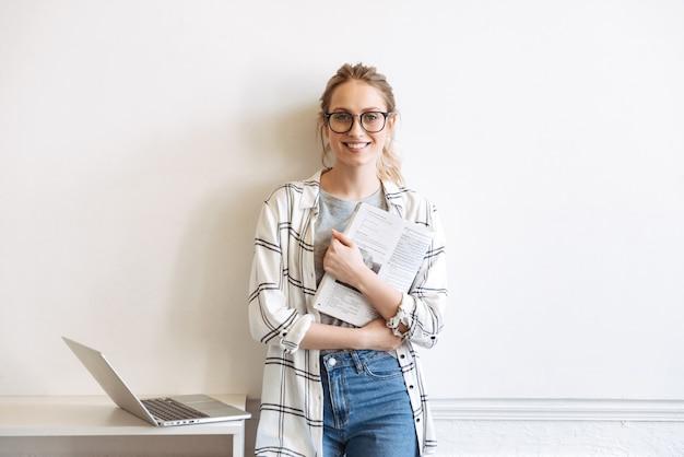 Mooie jonge student die met laptop binnenshuis studeert