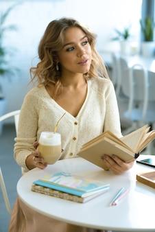 Mooie jonge student met open boek en glas cappuccino aan tafel zitten in gezellig café en genieten van koffiepauze