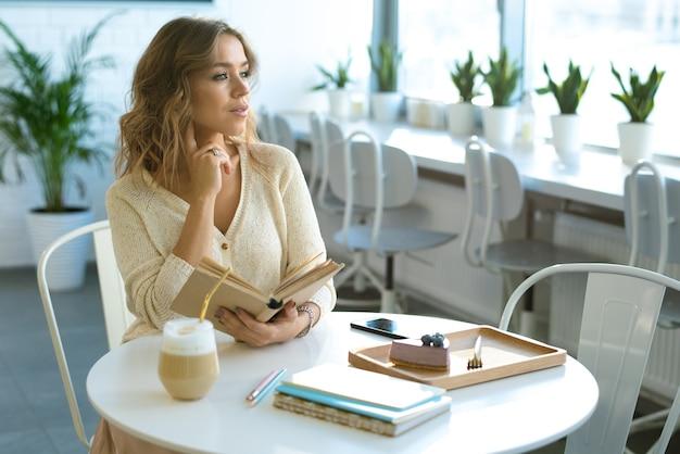 Mooie jonge student met open boek te wachten op haar vriend zittend aan tafel in café en koffiepauze