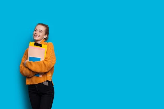 Mooie jonge student met rood haar en sproeten met enkele mappen op een blauwe studiomuur met vrije ruimte