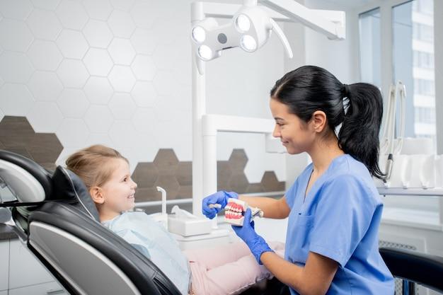 Mooie jonge tandarts of assistent in blauw uniform toont kleine patiënt in fauteuil hoe tanden goed te poetsen terwijl ze voor haar zit