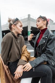 Mooie jonge tienermeisjes in modieuze kleding zitten op straat in de stad