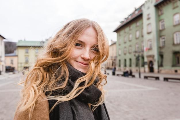 Mooie jonge toeristenvrouw die op straat loopt.