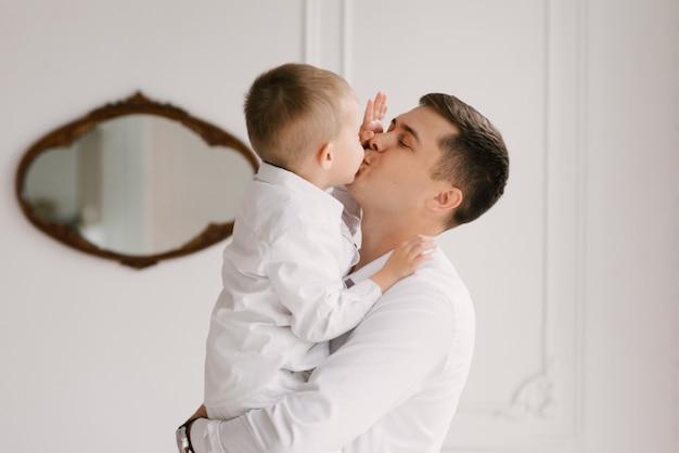 Mooie jonge vader en zoon knuffelen en spelen thuis in slimme kleding