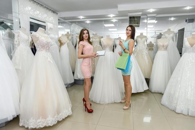 Mooie jonge verkoopvrouw die huwelijkskleding toont aan een klant