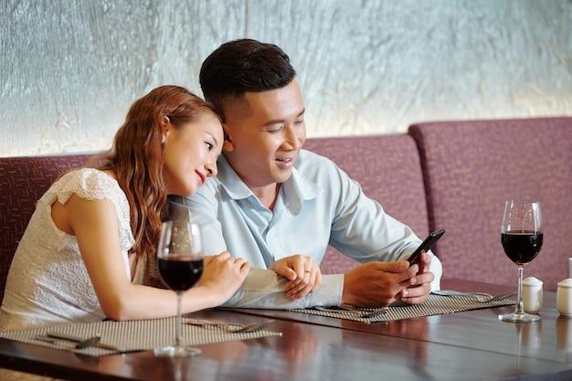 Mooie jonge verliefde koppels die tijd doorbrengen in een restaurant, ze wachten op eten en controleren nieuws op sociale media