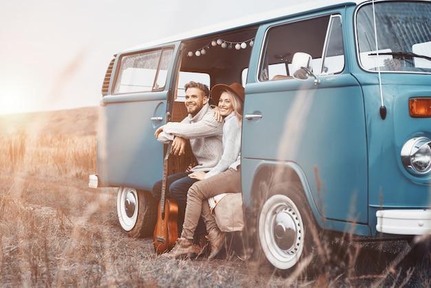 Mooie jonge verliefde paar bonden en glimlachen terwijl ze tijd doorbrengen in hun minibus buitenshuis