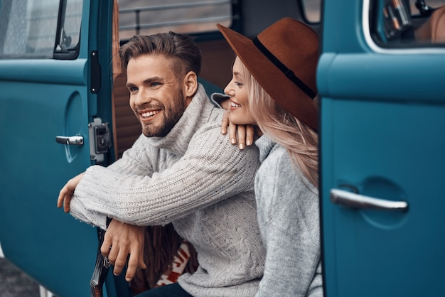 Mooie jonge verliefde paar bonden en glimlachen terwijl ze tijd doorbrengen in hun minibus