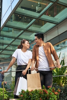 Mooie jonge verliefde paar boodschappentassen dragen en samen genieten.