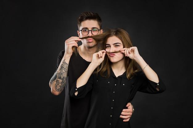 Mooie jonge verliefde paar maken nep-snor van haar terwijl je tegen de zwarte muur grappige snor.