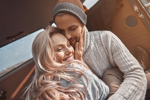 Mooie jonge verliefde paar omarmen en glimlachen terwijl ze tijd doorbrengen in hun minibus