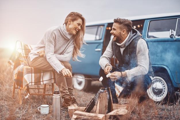 Mooie jonge verliefde paar picknicken bij het vreugdevuur zittend in de buurt van hun retro minivan