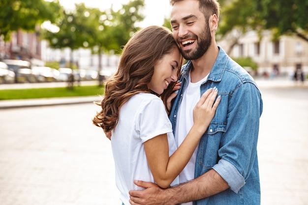 Mooie jonge verliefde paar wandelen buiten op de straat van de stad, omarmen